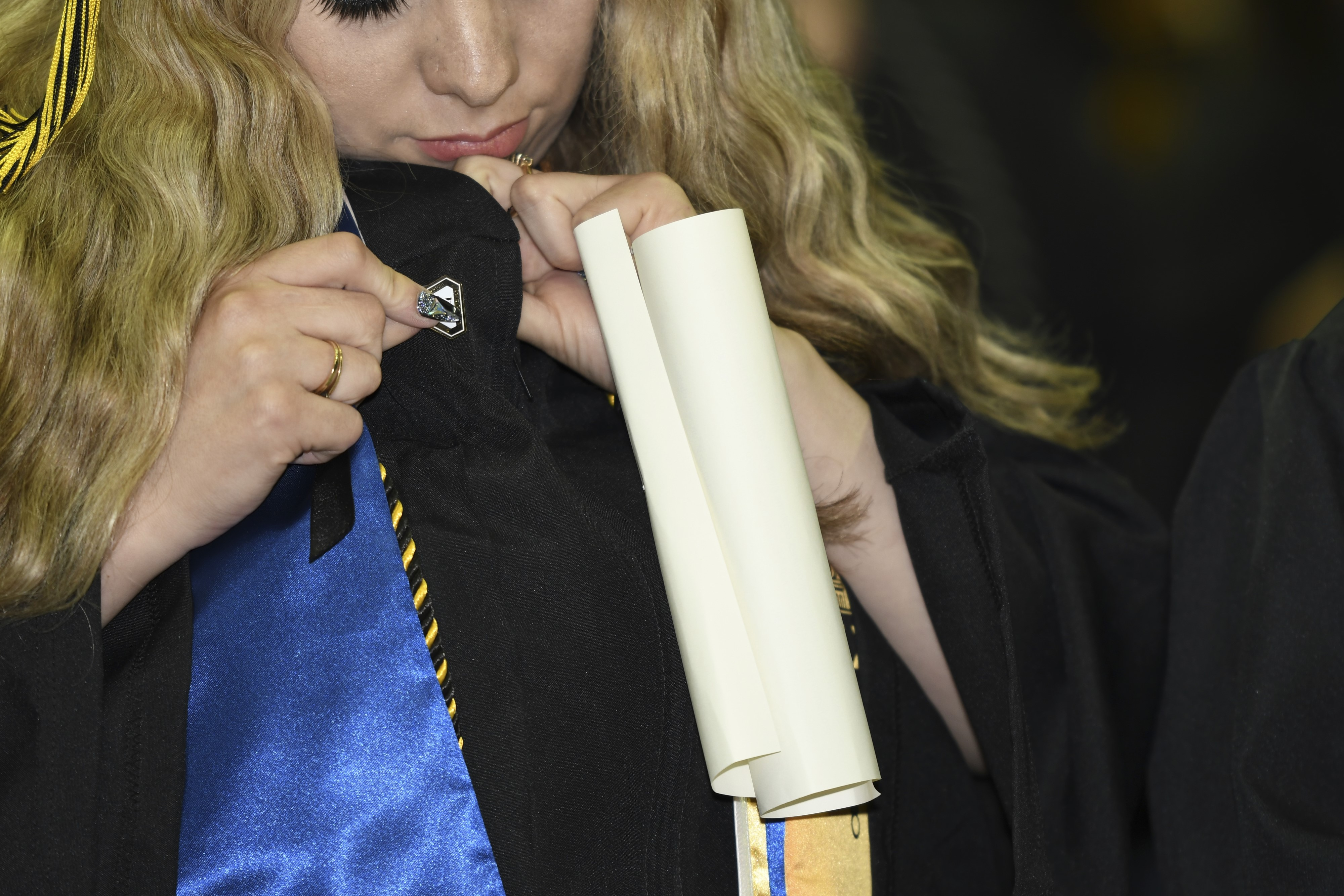 A new San Joaquin Delta College graduate puts on her alumni pin during the College's Commencement ceremony.