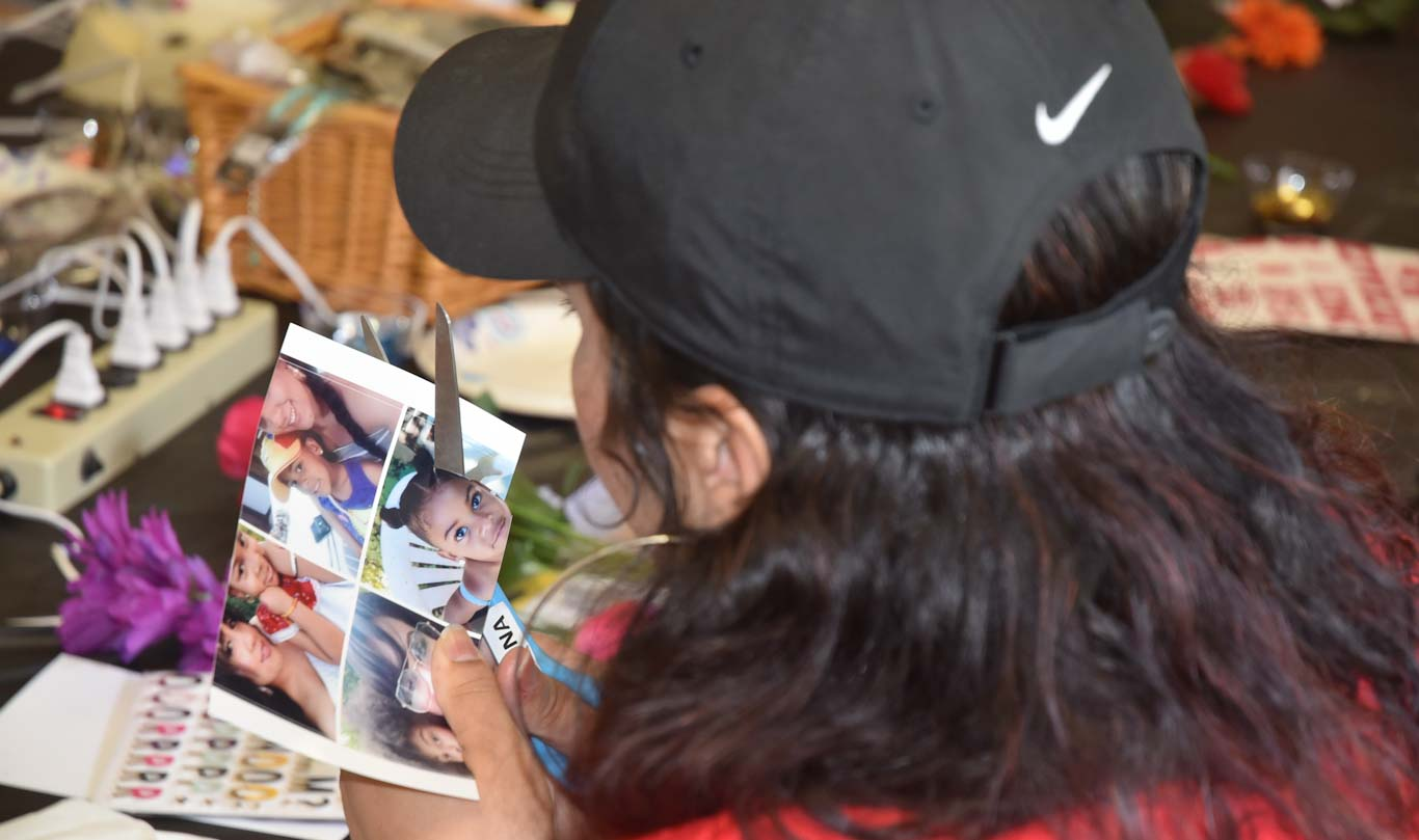 Vivian Medina cuts out a photo of her daughter, Valentina, for her Commencement cap. Vivian went to San Joaquin Delta College to help support Valentina.