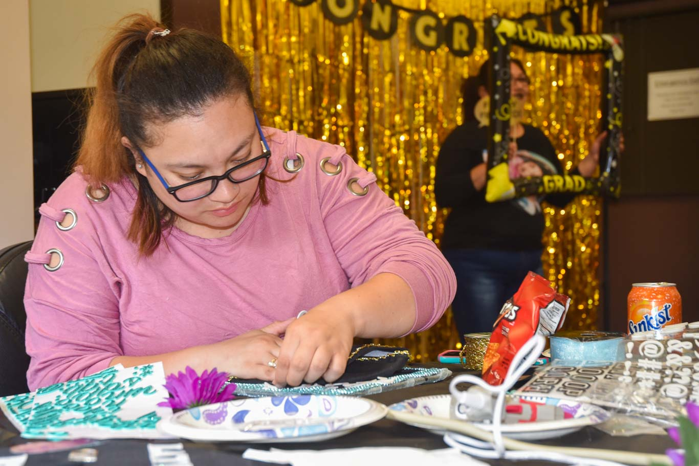 "San Joaquin Delta College student Sesilie Miranda works on her Commencement cap honoring her son Haven. ""I did it for him,"" she said."