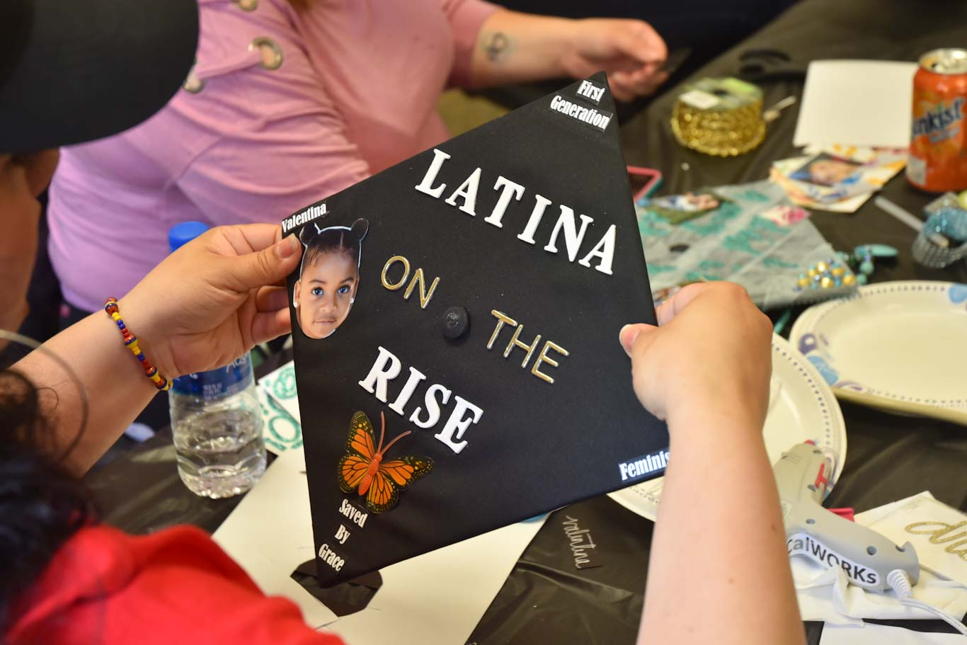"Vivian Medina's commencement cap includes a photo of her daughter Valentina and phrases that are important to her, like ""first generation,"" ""saved by grace"" and ""feminist."" She is graduating from San Joaquin Delta College next week."