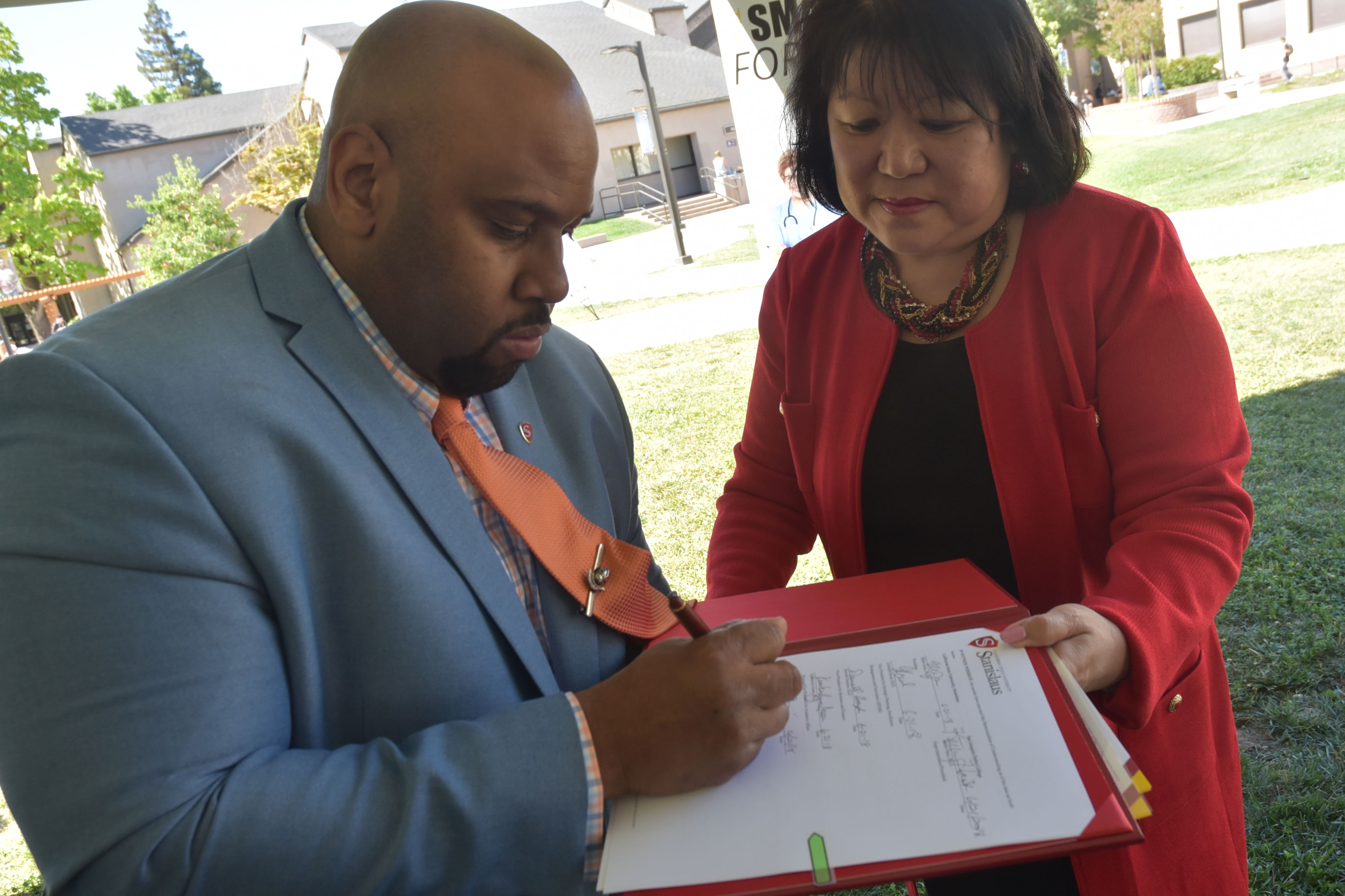 Faimous Harrison, dean of the Stanislaus State Stockton Center, signs the new agreement at San Joaquin Delta College on Thursday.