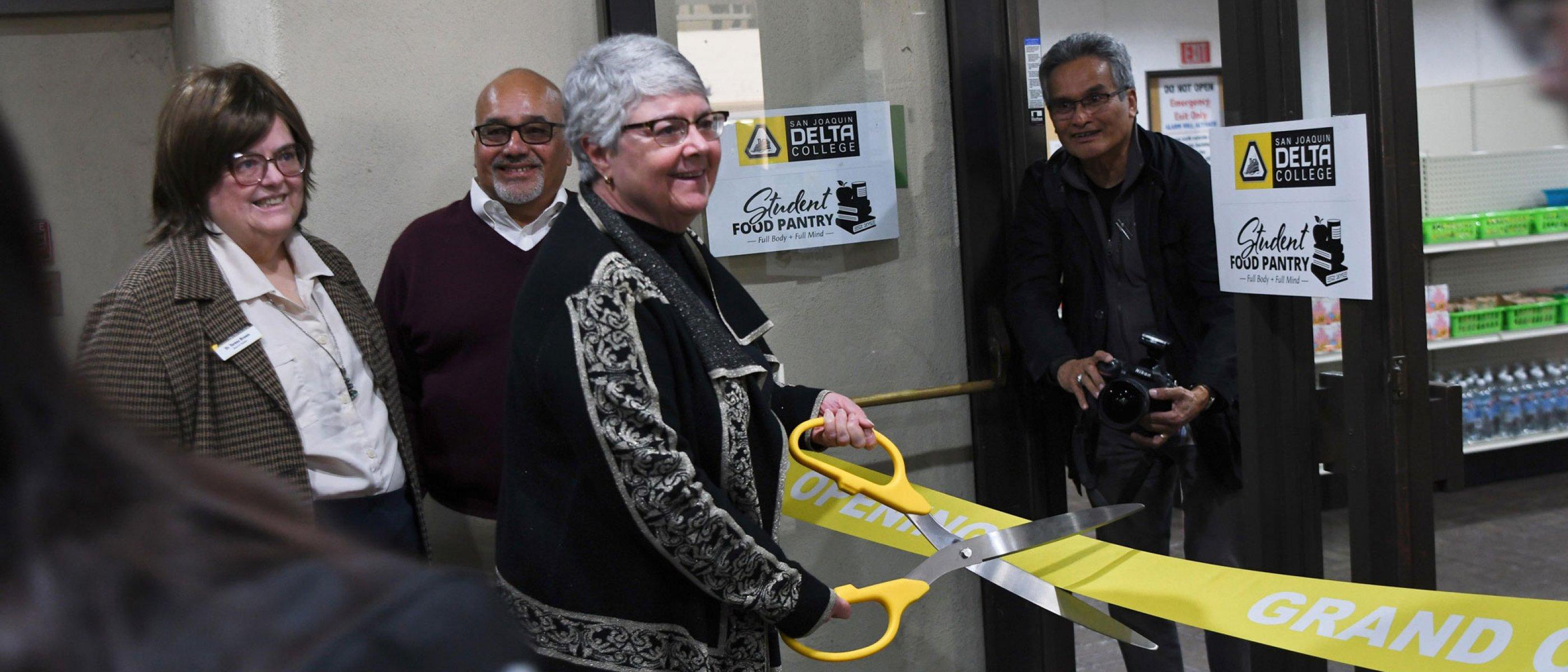 Kathy Hart cuts the ribbon at the Food Pantry Grand Opening