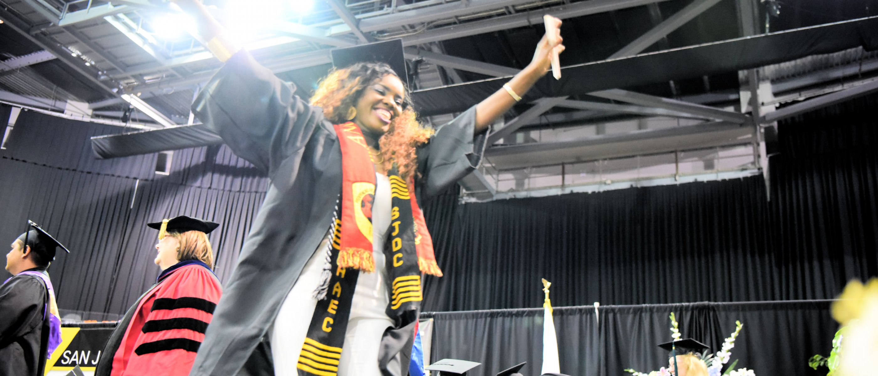 Delta grad walks across stage with diploma