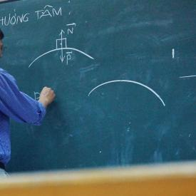 Teach performs physics equation on chalkboard